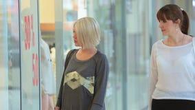 Le ragazze camminano intorno al centro commerciale ed osservano le vetrine archivi video
