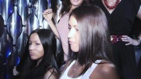 Le ragazze castane in camicia bianca ballano timido sul partito in night-club Mani di aumento intrattenimento video d archivio