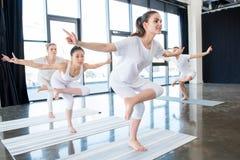 Le ragazze che fanno il gallo dorato sta su una posizione di yoga della gamba Fotografia Stock Libera da Diritti