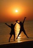 Le ragazze che saltano su un fondo del sol levante Immagini Stock