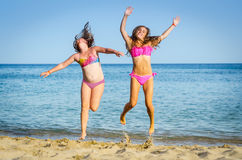 Le ragazze che saltano sulla spiaggia tropicale Fotografia Stock