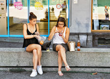 Le ragazze che si siedono sul banco fanno un spuntino nello svizzero Riviera di Montreux Fotografia Stock