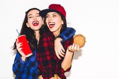 Le ragazze dei pantaloni a vita bassa con l'hamburger vegetariano che bevono una soda da paglia e dal divertiresi, felici, sorrid immagini stock libere da diritti