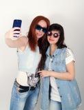 Le ragazze dei pantaloni a vita bassa di bellezza con cuffie, fanno il selfie su un telefono smorfia degli adolescenti Fotografia Stock