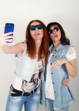Le ragazze dei pantaloni a vita bassa di bellezza con cuffie, fanno il selfie su un telefono smorfia degli adolescenti Fotografia Stock Libera da Diritti