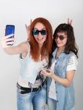 Le ragazze dei pantaloni a vita bassa di bellezza con cuffie, fanno il selfie su un telefono smorfia degli adolescenti Immagine Stock Libera da Diritti