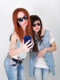 Le ragazze dei pantaloni a vita bassa di bellezza con cuffie, fanno il selfie su un telefono smorfia degli adolescenti Immagine Stock