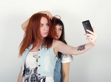 Le ragazze dei pantaloni a vita bassa di bellezza con cuffie, fanno il selfie su un telefono smorfia degli adolescenti Immagini Stock Libere da Diritti