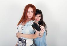 Le ragazze dei pantaloni a vita bassa di bellezza con cuffie, fanno il selfie su un telefono smorfia degli adolescenti Fotografie Stock Libere da Diritti