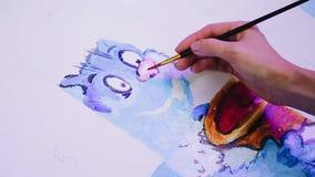 Le ragazze disegnano un gatto fresco blu su una tela bianca Mani del primo piano video d archivio