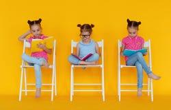 Le ragazze divertenti dei bambini hanno letto i libri su fondo giallo colorato fotografia stock libera da diritti