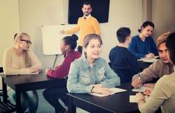 Le ragazze ed i ragazzi 15-18 anni stanno lavorando nei grandi gruppi Immagine Stock