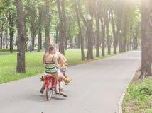 Le ragazze eleganti di boho felice guidano insieme sulle biciclette in parco Immagine Stock