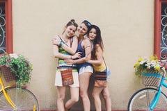 Le ragazze eleganti di boho felice posano con le biciclette vicino alla facciata della casa Immagine Stock