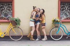 Le ragazze eleganti di boho felice posano con le biciclette vicino alla facciata della casa Immagini Stock