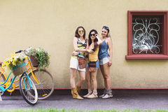 Le ragazze eleganti di boho felice posano con le biciclette vicino alla facciata della casa Fotografie Stock