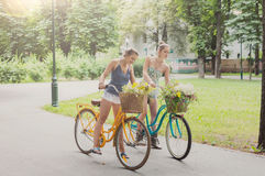 Le ragazze eleganti di boho felice riuniscono i fiori selvaggi sul giro della bicicletta Fotografia Stock