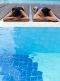 Le ragazze espongono al sole l'abbronzatura al raggruppamento Immagini Stock