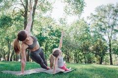 Le ragazze excercising in parco Stanno allungando insieme La donna ed il bambino stanno giudicando la loro mano sinistra alta e s Immagini Stock