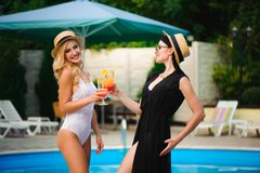Le ragazze felici con le bevande sull'estate fanno festa vicino allo stagno fotografia stock libera da diritti