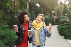 Le ragazze felici con portano via il caffè all'aperto Fotografie Stock
