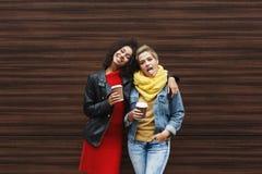 Le ragazze felici con portano via il caffè all'aperto Fotografia Stock