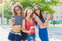 Le ragazze felici con portano via il caffè all'aperto Immagini Stock