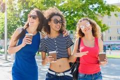 Le ragazze felici con portano via il caffè all'aperto Fotografia Stock Libera da Diritti