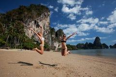 Le ragazze felici saltano alla bella spiaggia immagini stock