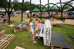Le ragazze giocano il piano all'aperto sulla terra verde del gioco Immagine Stock