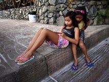 Le ragazze giocano un video gioco su uno smartphone mentre si siedono su un insieme dei punti Fotografia Stock Libera da Diritti