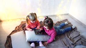 Le ragazze hanno compreso in uso della compressa e si siedono sul pavimento nella stanza luminosa con la ghirlanda sulla parete video d archivio
