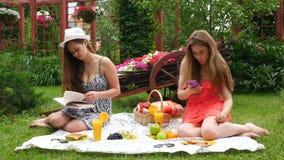 Le ragazze hanno un picnic, mangiano e leggono un libro stock footage
