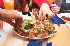 Le ragazze mangiano l'insalata di Caesar nel ristorante immagine stock