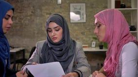 Le ragazze musulmane concentrate piacevoli del hijab sono parlanti e tenenti i documenti, sedentesi insieme nell'ufficio della lu stock footage