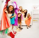 Le ragazze nascondentesi durante l'acquisto scelgono i vestiti Fotografia Stock
