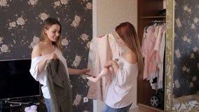 Le ragazze ottengono i vestiti dal gabinetto e lo misurano davanti allo specchio stock footage