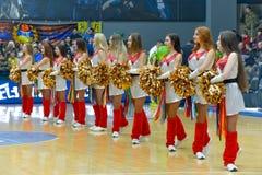 Le ragazze pon pon stanno ballando sul campo da pallacanestro Immagine Stock