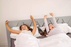 Le ragazze si alzano ed allungando sul letto Immagine Stock