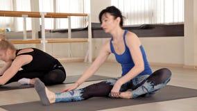 Le ragazze si esercitano in una classe aerobica con un sorriso L'istruttore di forma fisica lavora con una ragazza nella palestra stock footage