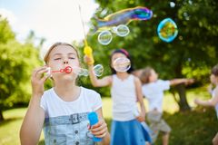 Le ragazze soffiano le bolle di sapone fragili nell'aria Immagine Stock