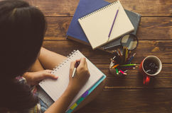 Le ragazze sono penna da scrivere sul taccuino sul pavimento di legno Immagine Stock
