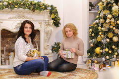 Le ragazze stanno aspettando le sorprese piacevoli del nuovo anno e sono sittin Fotografia Stock