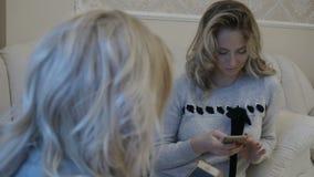 Le ragazze stanno facendo scorrere si alimentano i loro telefoni stock footage