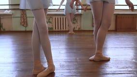 Le ragazze stanno nella terza posizione e cominciano a ballare nell'aula di balletto archivi video