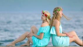 Le ragazze sveglie con le corone sulle loro teste stanno riposando sul fiume La giovane bella donna due in un vestito blu si sied stock footage