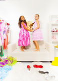 Le ragazze sveglie si tengono per mano e saltano sul sofà bianco Fotografie Stock