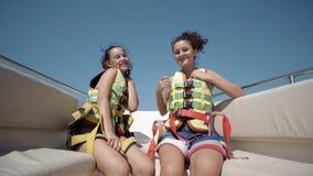 le ragazze teenager felici che indossano l'aumento delle cinture di sicurezza passano su nell'aria e si divertono sul giro con l' Immagine Stock Libera da Diritti