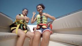 le ragazze teenager felici che indossano l'aumento delle cinture di sicurezza passano su nell'aria e si divertono sul giro con l' Fotografia Stock