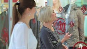 Le ragazze vengono alla finestra con i vestiti al centro commerciale stock footage